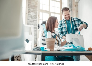 In atelier together. Good-looking stylish man and woman feeling nice working in atelier together