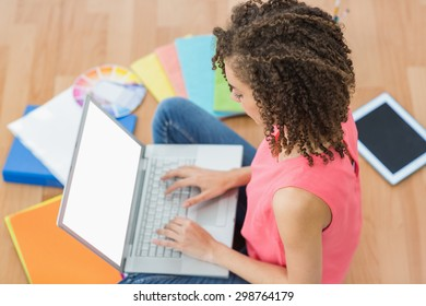 Atentive young creative businesswoman working on laptop
