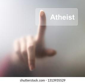 atheist button. Woman finger pressing a glass atheist button on grey background.