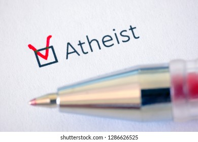 Atheist - checkbox with a tick on white paper with pen. Checklist concept.
