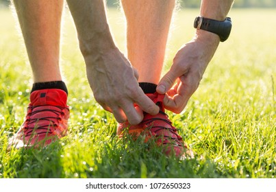 Athelete adjusting the laces of his running shoes in the grass. Shalloe D.O.F.