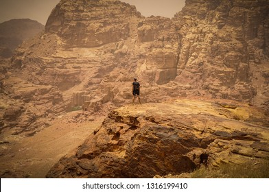 Atheletic guy standing in a rock, in a far distance, looking into the vastness of a rochy landscape