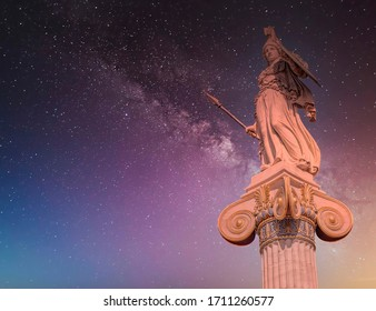 Athena the ancient Greek goddess of wisdom and knowledge statue under starry night sky in Athens Greece