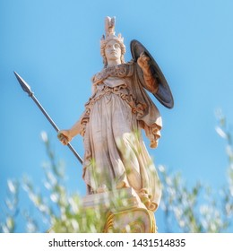 Athena marble statue with helmet, spear and shield, over some olive tree leaves, Athens Greece