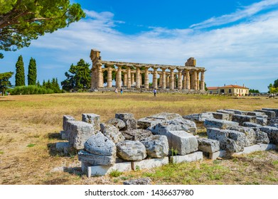 Athena (Minerva) Temple in Paestum, Salerno, Campania, Italy; at a bright summer morning. This place is famous for three Greek temples in Doric Order. Stones in the foreground.