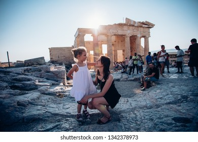 ATHENES, GREECE - AUGUST 10, 2017: group of tourits standing against ancient greek historical monument - Parthenon. Parthenon is a part of Athenian Acropolis.