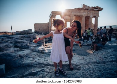 ATHENES, GREECE - AUGUST 10, 2017: group of tourits standing against ancient greek historical monument - Parthenon in the evening. Parthenon is a part of Athenian Acropolis.