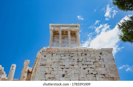 Athens Acropolis, Greece landmark. The Temple of Athena Nike low angle view at Propylaea gate entrance, blue cloudy sky in a spring sunny day.