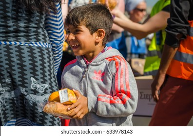 Athens APRIL 15:  Syrian boy receive oranges from Charitable Organizations in a refugee camp  April 15, 2016 in Athens.