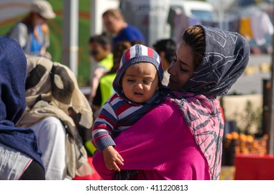 Athens - APRIL 17:  Mother holds in her arms her little baby on the background of the crowd of Syrian refugees   April 17, 2016 in Athens.