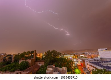 ATHENS, ATTICA, GREECE - MAY 2018: Intense stormy weather night with lightning bolts and thunderbolts against a dark cloudy sky.  Sudden seasonal weather changes often find city services unprepared.