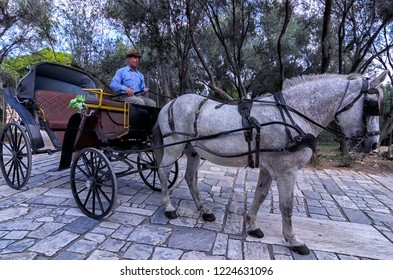 Athens, Attica / Greece - October 21, 2018: Coachman with his carriage waiting for tourists to take them a ride across the paved alleys below the Acropolis of Athens