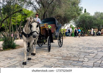 Athens, Attica / Greece - October 21, 2018: Coachman with his horse carriage is waiting for tourists to take them a ride across the picturesque paved alleys below and around the Acropolis of Athens