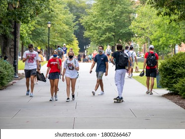 Athens, Georgia - August 20, 2020: During the COVID-19 pandemic, students wear face coverings while walking on campus on the first day of classes of the Fall semester at the University of Georgia.