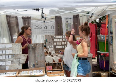 Athens, Georgia - June 22, 2019: A jewlery vendor talks with two young women at her booth in the artist market area during AthFest.