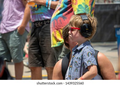Athens, Georgia - June 22, 2019: A young boy wears hearing protection while listening to a live music performance at the AthFest music and arts festival.
