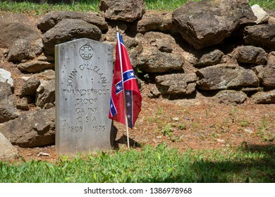 Athens, Georgia – May 2, 2019: A Confederate flag and inscribed stone mark the grave of a veteran of the Confederate States of America buried in historic Oconee Hill Cemetery.