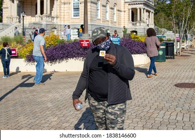 Athens, Georgia - October 16, 2020: A young African-American woman wearing a protective face mask holds up a sticker indicating she just voted during early voting for the November General Election.