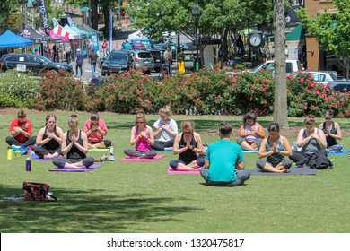 ATHENS, GEORGIA, U.S.A. – April 27, 2018: UGA students take a yoga class on the North Campus lawn on a beautiful spring afternoon as the Twilight Criterium Expo takes place on downtown College Avenue.