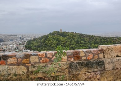 Athens, Greece, 10/01/2018.  View of Filopappos Hill or Moose Hill, with the Philopappos Monument, view from Acropolis fortress wall in inclement weather