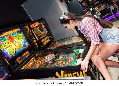 Athens, Greece, 12/19/2018, young pin up girl plays pinball in Athens pinball museum