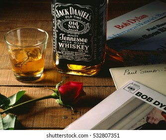 ATHENS, GREECE  2014: Jack Daniels bottle with a rose, a glass of whiskey and some LP records on wooden surface