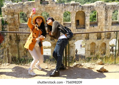 ATHENS, GREECE - 24 April 2015. Asian girls are taking selfie in front of the Odeon of Herodes Atticus in Athens,