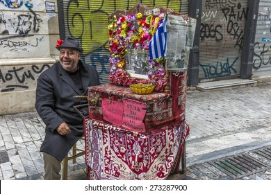 Athens, Greece - 9th April 2015. An organ grinder battles the economic climate with his colorful music box on the graffit-laden streets.
