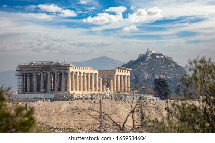 Athens, Greece. Acropolis Parthenon temple seen from Philopappos Hill, blue cloudy sky. Lycabettus hill background