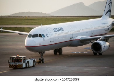 """Athens, Greece - April 19, 2017. An Aegean Airlines Airbus A321-231 (SX-DGP) hooked up to a tow tractor, at the apron of Athens International Airport """"Eleftherios Venizelos""""."""