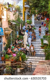 Athens, Greece - August 2, 2012: People dining outside on the stairs in the Plaka district of Athens.