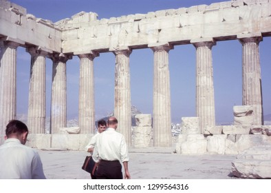 Athens, Greece - Circa, 1960s: The Parthenon. Ancient monument ruins on the Acropolis. With male tourists visiting the site. Vintage photo from a 35mm slide.