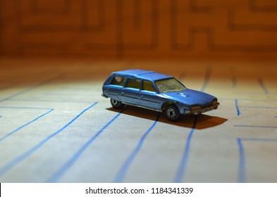 Athens, Greece – December 16, 2015: Old Matchbox Toy car of the 70's, running on a wooden deck with the pattern of a labyrinth, designed with a blue pen.
