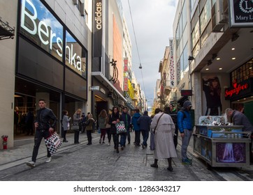 Athens, Greece. December 21, 2018: Ermou Street is the central shopping street of the city of Athens with typical Greek architecture on a sunny winter day with tourists and locals walking and shopping
