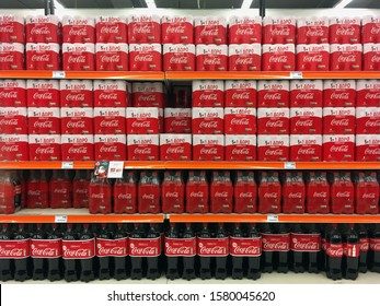 Athens, Greece - December 3, 2019: Packs of cans and bottles of Coca Cola soft drink in supermarket aisle.
