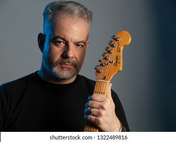 ATHENS, GREECE – FEBRUARY 11 2019: Man holding a Fender Squier Stratocaster electric guitar isolated on neutral background, studio shot