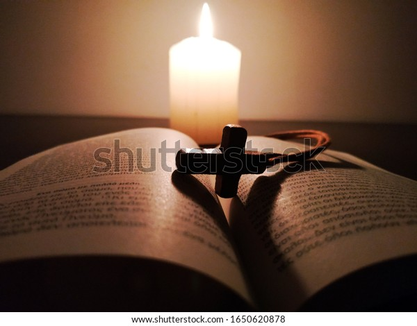 Athens, Greece - February 2020: Christian cross, Bible and a candle on wooden background