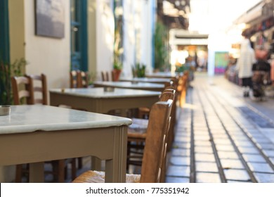 Athens, Greece. Greek tavern empty tables and chairs in a row, blur pedestrian and market background