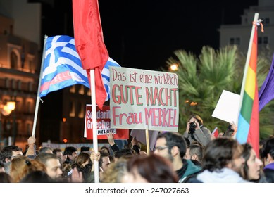 "Athens, Greece Jan. 25, 2015 Supporters of Syriza left wing party with flags outside Athens University. The baner says:""This is really good night Mrs Merkel"". Syriza, won Sunday's general election."