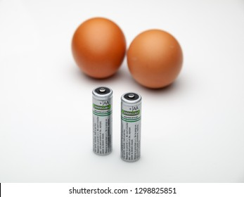 ATHENS, GREECE – JANUARY 29 2019: Two AA rechargeable batteries and two out of focus eggs isolated on white background