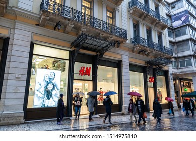 Athens, Greece - January 4, 2019: Display of a HM store at night with people around in Athens, Greece