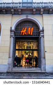 Athens, Greece - January 4, 2019: Entrance of a HM store at night with people around in Athens, Greece