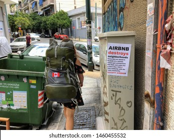 Athens, Greece - July 14, 2019: A tourist and Airbnb user walking past an anti-Airbnb posted in the Koukaki area of Athens, Greece.  Many locals worry the company raises the price of rent in Athens.