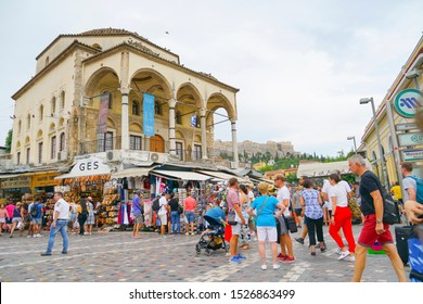 Athens Greece - July 15 2019; Archaeological site  acropolis on hill behind crowds throng around Plaka square and tourist trinkets vendors.