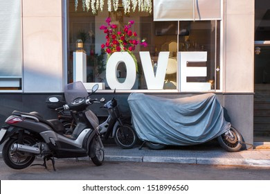 ATHENS, GREECE - JULY 18, 2019: Concept of Love. Shop window with big letters LOVE , red flowers and motorbikes, motorcycle outdoor near the window. Conceptual photo. Love theme. Rock style background
