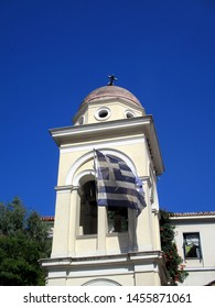 Athens / Greece - July, 19, 2019: aftermath of the earthquake, fallen cross on the church in the center of Monastiraki square (Ekklisia Kimisi Theotoku Mitropoleos). Taken around 4PM. Greek flag below