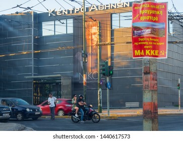 Athens, Greece, July 2019: Streets of the Athens district of Tavros with cars, motorcycles and Communist party poster KKE summer evening at sunset