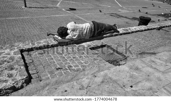 Athens, Greece - July 2020: Black and white photograph of a homeless man sleeping in the streets of Athens.