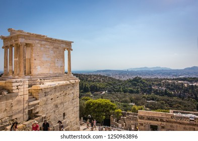 ATHENS, GREECE JULY 24 2016: The Temple of Athena Nike at the entrance of The Acropolis with tourists and a beautiful panoramic view of Athens at the far back of the temple.