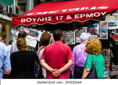 ATHENS, GREECE - JULY 4TH, 2015: Group of people reading the newspapers on July 4th, 2015, in Athens, Greece.  Headlines refers about possible results of the referendum on July 5th, 2015, in Greece.
